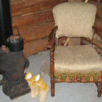 Detail of trapper's wood stove for heating and cooking, chair and boots.